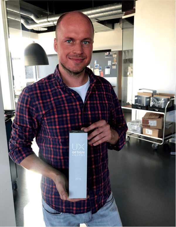 Our colleague Sebastian proudly holds the UX Award, which he and his team received for the STAT Diagcore product from Qiagen.