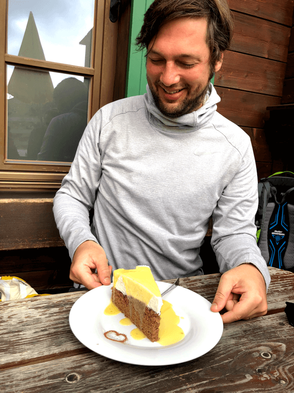 our colleague Bastian is happy about the piece of cake in front of him during the Imago hiking day.