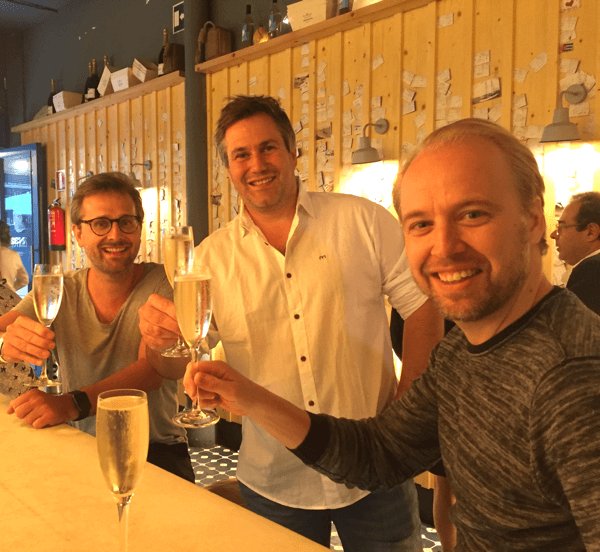 Our colleagues Jonas, Alexander and Alex are drinking sparkling wine in a bar.