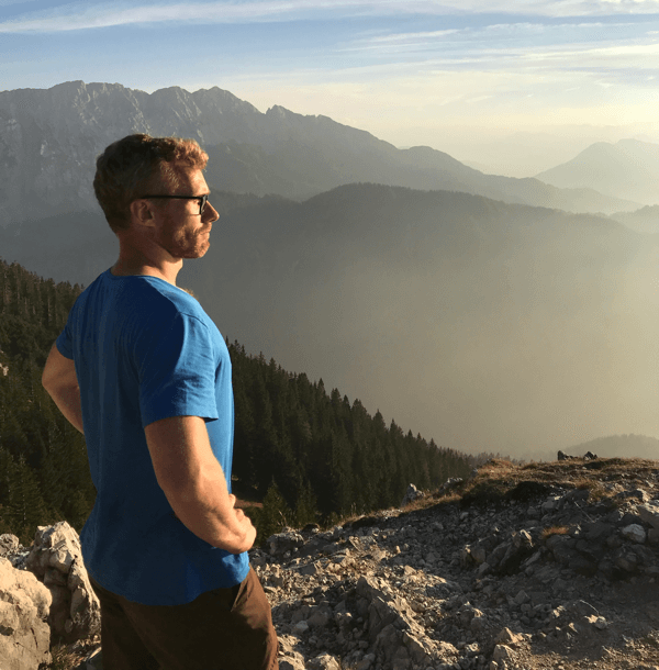 During the Imago hiking day, our colleague Arno stands with proudly swollen chest on the mountain he has just climbed and looks into the distance.
