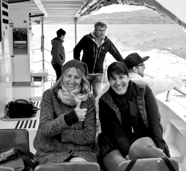 Our colleagues on a boat tour: Veronika and Miriam are sitting and laughing at the camera, Micky sits behind them with his backs to the camera and Alexander looks meaningfully into the distance.