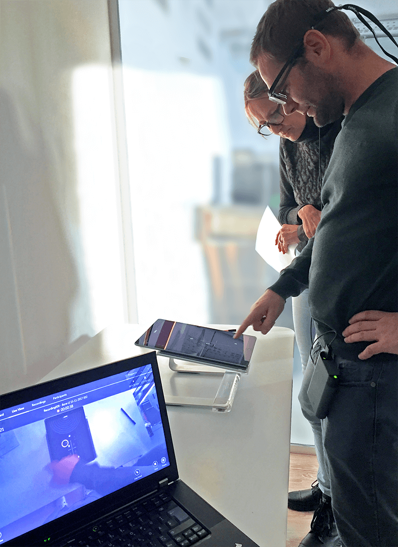 In our internal usability lab, a test person, led by our colleague Veronika, tests the BORA Pure user interface on a tablet. The participant wears eye-tracking glasses.