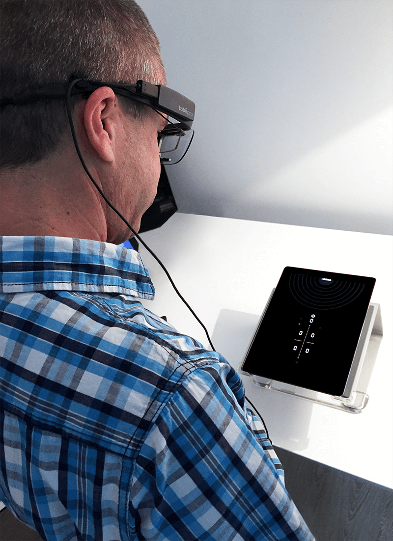 In our internal usability lab, a test person is testing the BORA Pure user interface on a tablet. The test persons wears eye-tracking glasses.