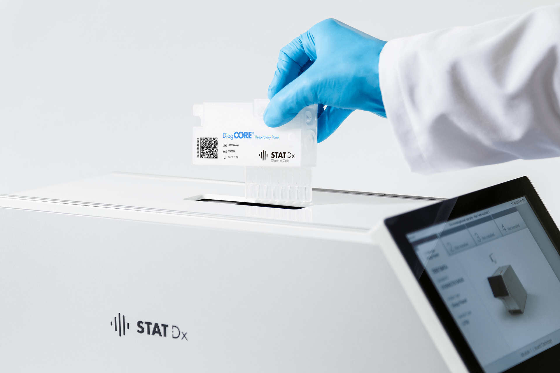 A laboratory assistant is placing a sample to be analyzed in Qiagen's QIAstat Analyzer.